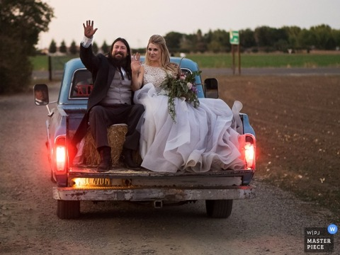Wedding photograph of a Sacramento bride and groom riding off in the back of a vintage pickup truck
