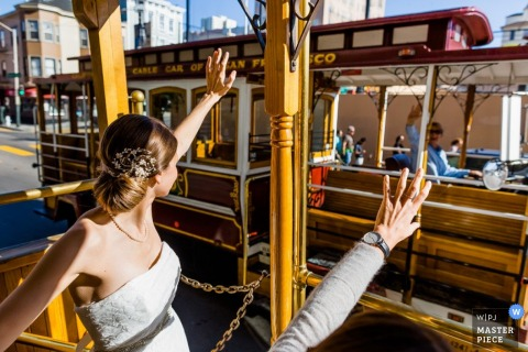 Wedding photograph of bride waving from trolley | Wedding day moments captured in San Francisco