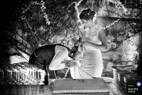 Arezzo groom kisses the brides dress at the reception | Tuscany wedding photo