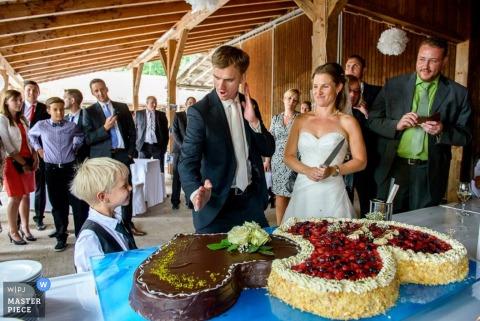 Le marié munichois montre que le karaté se déplace vers le petit garçon devant le gâteau | Photographie de mariage en Bavière