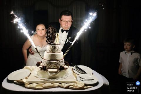 Narzeczeni Mielec zdmuchują świeczki na torcie weselnym w recepcji Podkarpackie fotoreportaże ślubne