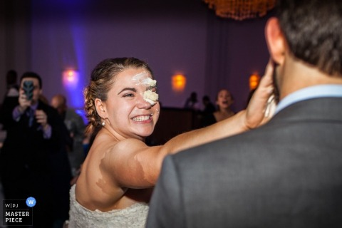 Montana bride and groom smile as they smash cake into each others face | United States wedding photography
