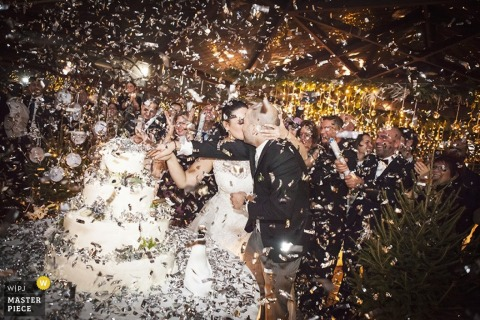 Milan bride and groom kiss as confetti surrounds them while cutting the cake | Lombardy wedding photojournalism