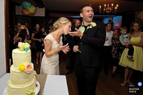 Wedding reception photography of bride and groom feeding cake to each other | coverage for Devon wedding receptions