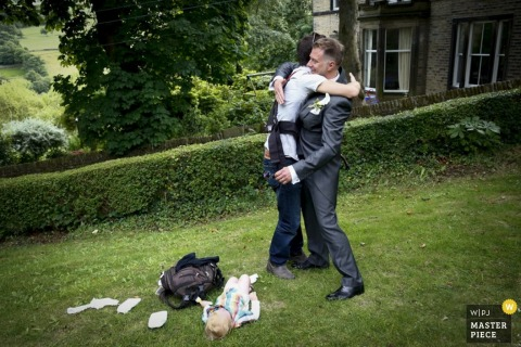 London guest hugs the groom before changing his baby | England wedding reportage photo