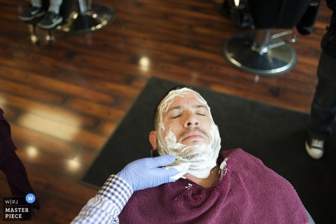 The groom gets a cut and a shave at the barber shop before his wedding ceremony | New Jersey Wedding Photography