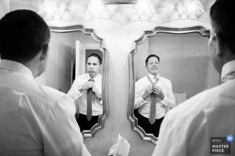Philadelphia groom and groomsmen getting dressed in the mirror before the wedding | Pennsylvania wedding photography