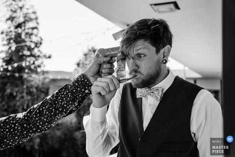 San Diego groom brushes his teeth as a bubble gun is pointed at him | California wedding photo