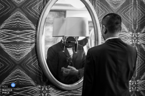 Beijing groom making sure his tux looks good in the mirror before the ceremony | China wedding photojournalism