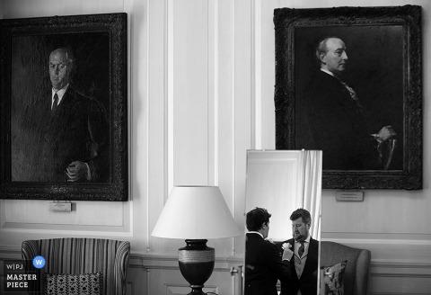 London groomsmen helping the groom get ready for the wedding | England wedding photo