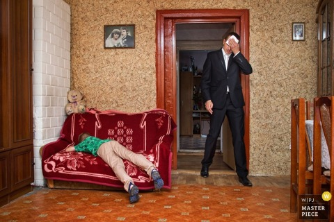 Krakow groom wipes off sweat as little boy next to him sleeps on couch at wedding | Malopolskie wedding photographer
