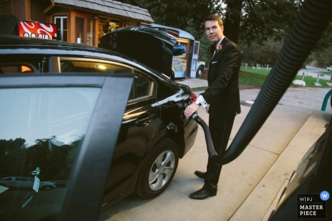 Fotografia di nozze di San Francisco dello sposo che riempie l'automobile di gas durante la preparazione prima della cerimonia di nozze di CA.