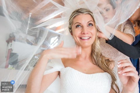 Venice wedding photograph of bride fanning herself as veil goes on