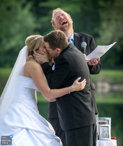 Chicago bride and groom kiss while priest laughs during outdoor ceremony | Illinois wedding photo