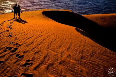 Sao Paulo Desert sand Engagement Photo. This couple walks in the warm red dunes above the ocean.