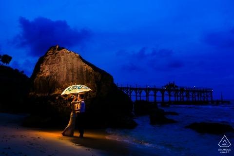 Paraplu en een licht op het strand na zonsondergang. Paarportretten door Hangzhou Engagement-fotograaf