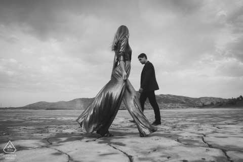 a Chelyabinsk couple walking on the cracked desert floor for engagement portraits