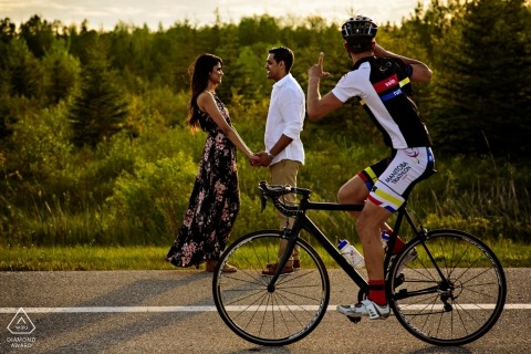 Canadian Engagement Photo. A bicyclist snaps a photo of this engage couple posing by the roadside.