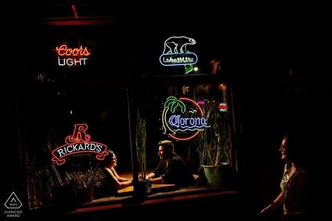 MB, Kanada Engagement Fotograf. Portraitsitzung in der Bar mit Neonbierzeichen.