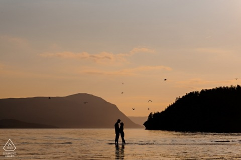 Manitoba Engagement Photography. Wading into the water, a couple embraces at sunset.