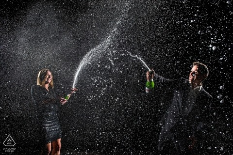 Colorado Engagement Photograph of a couple spraying champagne into the night air.