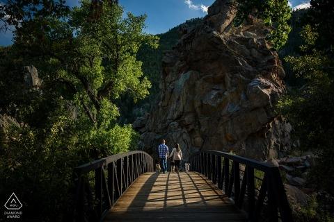 CO-voorhuwelijk Foto van een paar dat over een houten brug in het bos loopt.