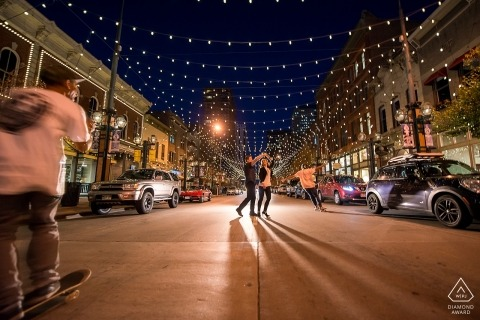Boulder Engagement photography at night in the middle of the street with passing skateboarders.