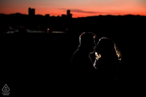 Colorado Engagement Fotograaf werkt een nachtportret sessie met een enkel licht en de skyline van de stad