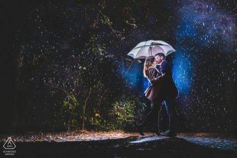 Photographie de fiançailles d'un couple sous la pluie, éclairé sous un parapluie | Hesse photographe de pré-mariage