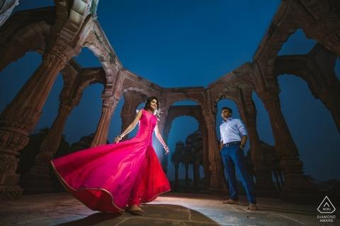 Foto pre-matrimonio di Mumbai. Spinning nel suo vestito rosso in questo ritratto illuminato.