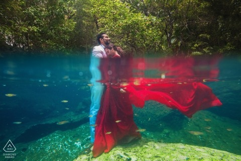 Mumbai Engagement Photo. Half onder water met haar rode jurk en verloofde.