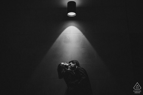 Black and white portrait of a couple kissing under a solo light. East Midlands Engagement Photographer