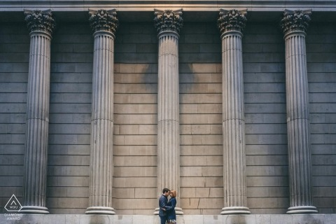 Set before a backdrop of architectural columns, a couple poses for an engagement photo | UK engagement photographer
