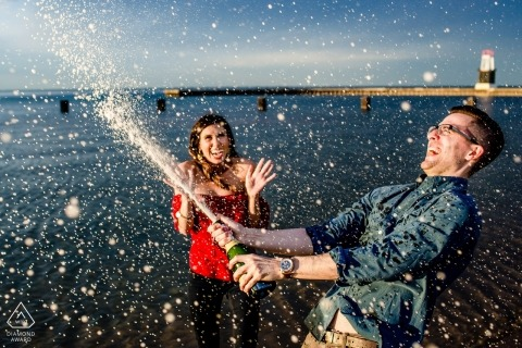 Engagement Portrait of couple by the lake spraying champagne | Chicago engagement photographer