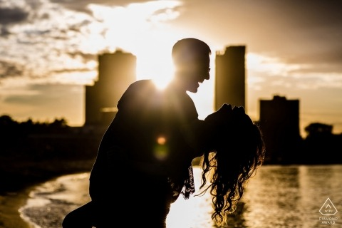 A Chicago romantic dip for this sunset engagement portrait before the city skyline