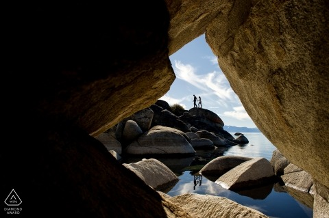Framed by rocks, a couple walks on a rocky waterside during a wedding engagement shoot | Lake Tahoe wedding photographer