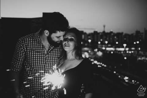Federal District wedding engagement photos at night in the city with sparklers for Brazil couples