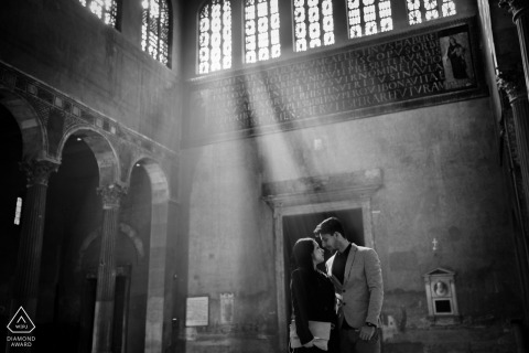 Italian Engagement Photographer. Sunlight streams through the high windows during this indoor portrait in black-and-white.