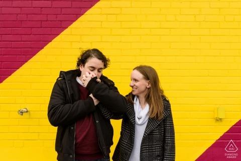 Photos de fiançailles de mariage à Montréal par un mur de briques peintes par un photographe de Montréal