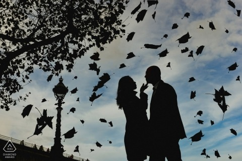 Silhouette of engaged couple within a shower of leaves during a pre-wedding photo session