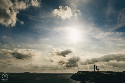 Derbyshire Engagement Photo of a silhouette couple against the sky filled with clouds at the ocean.