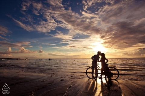 Malacca Engagement Photography - couple kissing on the boardwalk near the water - Sunset silhouette with the bike