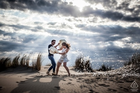 Down feather pillow fight at the beach in the sand below dramatic clouds during this Miami Florida engagement shoot