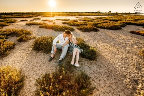 Prague Engagement Photo. The couple sit on the dry ground in the field as the sun is setting.