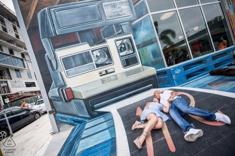 Miami Florida couple Pose for an engagement photograph below a Polaroid camera Wall mural