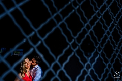 Mesh wire fence portrait of a couple by a Valencia, Spain Engagement Photographer