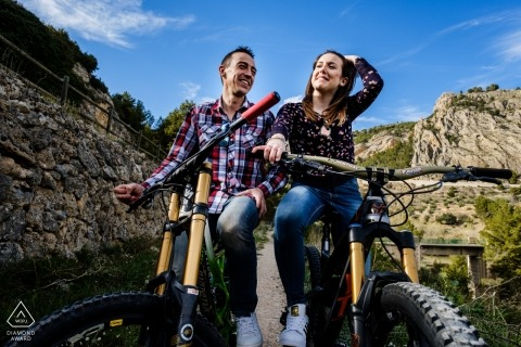 Mountain biking couple stop for a lifestyle portrait during their prewedding photo session | Alicante wedding photographer