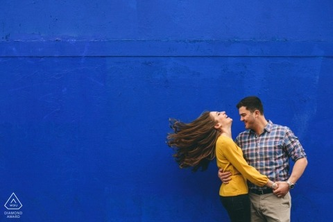 Engagement photograph of couple against a bright blue backdrop | South Bank prewedding sessions