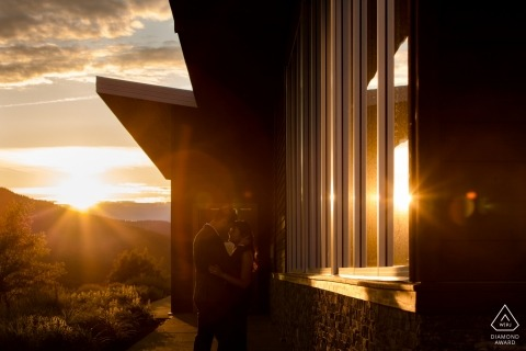 Kelowna architecture and sunshine flares add to this dramatic engagement portrait