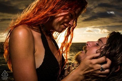 Portrait de couple éclairé à la plage au coucher du soleil par un photographe de fiançailles à Madrid